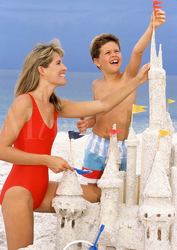 Mother and son building sand castle at beach