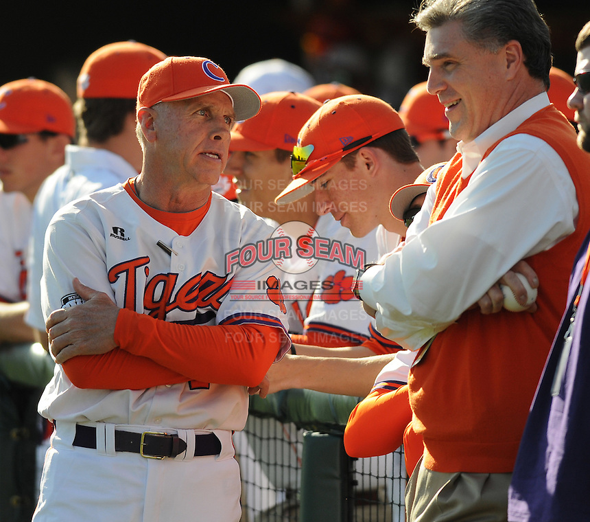 Head coach Jack Leggett of the Clemson Tigers talks with athletics director Dan Radakovich before a game against the William & Mary Tribe on Opening Day, Friday, February 15, 2013, at Doug Kingsmore Stadium in Clemson, South Carolina. Clemson won, 2-0. (Tom Priddy/Four Seam Images)