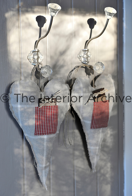 A pair of rustic stuffed linen hearts hang from glass hooks in a bedroom