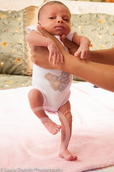 Newborn baby girl 12 days old held upright reflex stepping