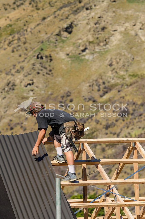 Roofer applying corrogate to timber house frame in Queenstown - stock photo, canvas, fine art print