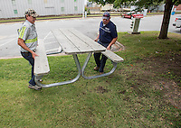 NWA Democrat-Gazette/J.T. WAMPLER Carl Pullum (left) and  Wendall Brewer, both employees of Rogers Parks and Recreation, move a table at Frisco Park in downtown Rogers. The park will be the site of Frisco Fest today(FRIDAY) and Saturday. The festival kicks off at 5:00 P.M. with live music until 11:00 P.M. Saturday events start at 7:00 A.M and go through 11:00 P.M. For more information go to: www.mainstreetrogers.com/friscofestival-aspx/frisco-festival-schedule-events-2014/