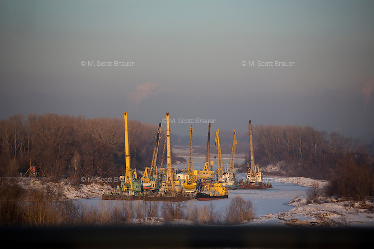 Cranes on boats float in the White River in Ufa, Bashkortostan, Russia.