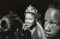 UPINGTON, SOUTH AFRICA - FEBRUARY 9: An unidentified girl (C) is crowned at a beauty pageant held at a local club February 9, 2002 in Loisevale, Upington, South Africa. Loisevale is a poor and destitute black township where unemployment is high. A number of social problems exist including domestic violence and alcohol abuse. Baby Thsepang, an eight-month-old baby, was raped by her father in Louisevale in October 2001. The baby rape shocked the country. South Africa is struggling with an increasing number of rapes and sexual abuse of young children. In addition, the country has the highest number of rapes in the world. (Photo by Per-Anders Pettersson)