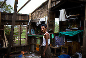 Houses were badly destroyed by the cyclone Nargis. Here, the house owner poses inside his broken down house in Falan village in Kyauktan township. Many took shelter in the Middle school that has been temporarily transformed as a refuge for 18 families and 140 people. .