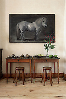 In the living room two antique school desks with matching stools serve as side tables