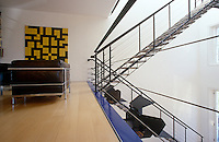Next to the dramatic open staircase of a house designed by Richard Rogers a leather and chrome Corbusier sofa arranged next to a large abstract painting creates an intimate seating area