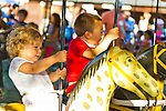 Old Bethpage, New York, U.S. 29th September 2013.  Young children enjoy riding an old-fashioned merry-go-round at The Long Island Fair. A yearly event since 1842, the county fair is now held at a reconstructed fairground at Old Bethpage Village Restoration.