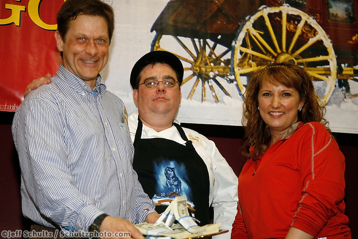 Martin Buser recieves the Millenium hotel first to the Yukon award from chef Mick Hug and Brooke McGrath at the Nome awards banquet.