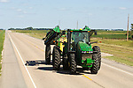 John Deere tractor with spray rig, driver and his young son on highway ND 13