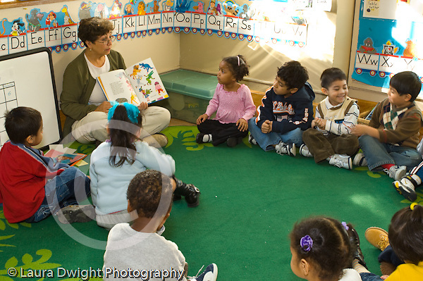 Preschool Headstart 4 year olds New York City circle time female teacher reading book to group of children horizontal
