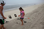 Long Beach Island, NJ - June 30, 2013 :  At dawn, Joe Kaelin takes his granddaughter Breonna Jackson, 7, from New Gretna, NJ, metal detecting for the first time along Beach Haven on Long Beach Island, NJ on June 30, 2013. Joe has been visiting LBI for the summer for the past nine years. People are returning to the beaches for the summer after recovery efforts post Superstorm Sandy.