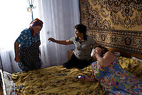 REPUBLIC OF MOLDOVA, Gagauzia, Vulcanesti, 2009/06/30..Viera and her sister Anna and the stepmother mother of Viera, Fiedorova in the bedroom of her home in Vulcanesti. In each gagauz family, someone from earning a living abroad. Viera works in Moscow and his sister in Turkey. On the occasion of the summer works in fields, everyone ends up in the family home..© Bruno Cogez / Est&Ost Photography..REPUBLIQUE MOLDAVE, Gagaouzie, Vulcanesti, 30/06/2009..Viera et sa soeur Anna et la belle mère de Viera, Fiedorova dans la chambre à coucher de la maison familiale à Vulcanesti. Dans chaque famille gagaouze, quelqu'un part gagner sa vie à l'étranger. Viera travaille à Moscou et sa soeur en Turquie. A l'occasion des travaux d'été dans les champs, tout le monde se retrouve dans la maison familiale..© Bruno Cogez / Est&Ost Photography