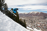 USA, Colorado, Aspen, skier getting air on a trail called Corkscrew with the town of Aspen in the distance, Aspen Ski Resort, Ajax mountain