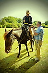 Old Bethpage, New York, USA. September 28, 2014. Rough Rider BERNADETTE MCHUGH, astride Noche the black Spanish Mustang, holds Elwood, her Jack Russel dog, who is licking WALTER KEHOE, of Syoseet, on crutches, at the 172nd Long Island Fair, a six-day fall county fair held late September and early October. A yearly event since 1842, the old-time festival is now held at a reconstructed fairground at Old Bethpage Village Restoration.
