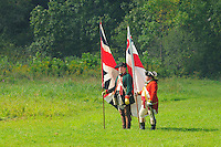 British redcoat Captain and officer of Butler's Rangers, a provincial Loyalist unit, stand with regimental colors during a Revolutionary War re-enactment at Fort Ticonderoga, New York, USA.