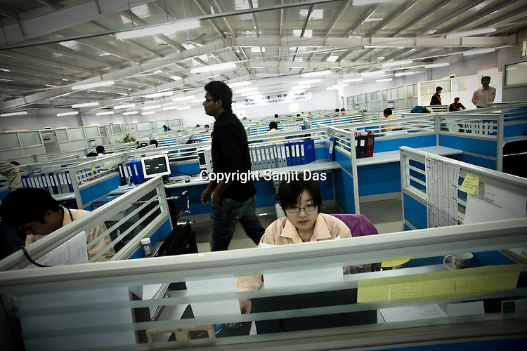 24 year old Chinese interpreter, Cui Yan seen in her cubical at work in the Adani Power plant in Mundra port industrial city of Gujarat, India. Indian power companies have handed out dozens of major contracts to Chinese firms since 2008. Adani Power Ltd have built elaborate Chinatowns to accommodate Chinese workers, complete with Chinese chefs, ping pong tables and Chinese television. Chinese companies now supply equipment for about 25% of the 80,000 megawatts in new capacity.