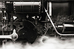 A black and white close up of a steam engine