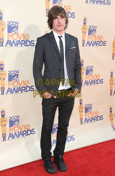 ZAC EFRON.The 2009 MTV Movie Awards held at Universal Ampitheatre  in Universal City, California, USA..May 31st, 2009 .full length suit jacket hand in pocket jeans denim tie grey gray.CAP/DVS.©Debbie VanStory/Capital Pictures.