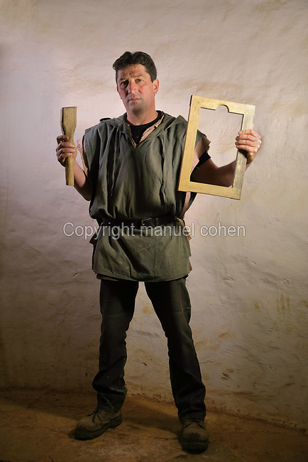 Bruno Feval, tile maker on the Guedelon project since 02/04/2009, wearing medieval costume and holding a tile mould and mallet, at the Chateau de Guedelon, a castle built since 1997 using only medieval materials and processes, in Treigny, Yonne, Burgundy, France. The Guedelon project was begun in 1997 by Michel Guyot, owner of the nearby Chateau de Saint-Fargeau, with architect Jacques Moulin. It is an educational and scientific project with the aim of understanding medieval building techniques and the chateau should be completed in the 2020s. Picture by Manuel Cohen