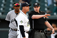 Manager Pedro Lopez (32) of the Columbia Fireflies talks with home plate umpire Forrest Ladd while Jolbert Cabrera of the Augusta GreenJackets looks by on Opening Day, Thursday, April 5, 2018, at Spirit Communications Park in Columbia, South Carolina. Columbia won, 4-2. (Tom Priddy/Four Seam Images)