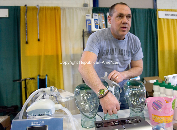 TORRINGTON CT. 04 April 2014-040414SV05-Mike Patterson, owner, sets up the Doyle&rsquo;s Medical Supply booth at the Northwest Connecticut Chamber of Commerce Northwest Expo at the Armory in Torrington Friday. <br /> Steven Valenti Republican-American