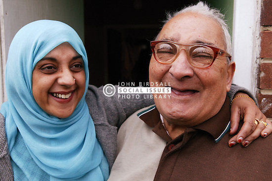 Asian carer with elderly Asian man happy and laughing outside at home, ***NOT TO BE USED IN THE EAST MIDLANDS***