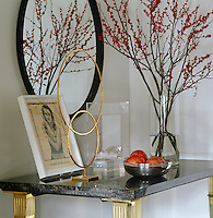 A brass sculpture by Keith Coventry and a framed Calvin Klein advertisement featuring Kate Moss are displayed on the hall console table