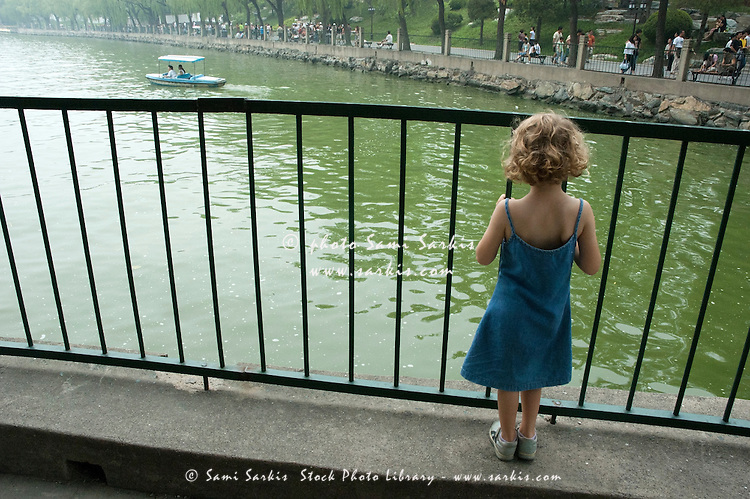 Blond girl stands watching the boats through the railings on the lake in Behai Park, Beijing, China.