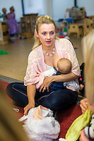A mother breastfeeds her young baby while talking to other mums at a drop-in breastfeeding support centre.<br /> <br /> Hampshire, England, UK<br /> 12/11/2014<br /> <br /> &copy; Paul Carter / wdiip.co.uk
