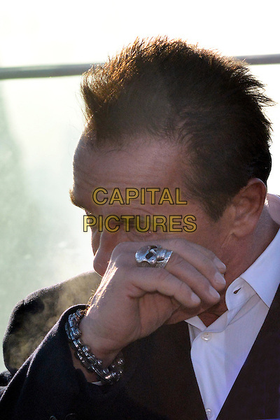"""Arnold Schwarzenegger.""""The Last Stand"""" Moscow Premiere, Hotel """"The Ritz Carlton"""", Moscow, Russia..January 23rd, 2013.headshot portrait black white shirt hand arm looks sad upset crying tears hand ring silver skull wiping eye eyes .CAP/PER/GU.©GU/PersonaStars/CapitalPictures"""