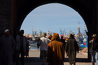 ESSAOUIRA, MOROCCO - MAY 11 : A view from behind of the Porte de la Marine on May 11, 2009 in Essaouira, Morocco. Men in traditional hooded Djellabas walk through the arch of the Porte de la Marine, built in 1771,  towards the boats. Essaouira, on the windswept Atlantic coast, was re-built in the 18th century by French architect Theodore Cornut to the orders of Sultan Ben Abdullah. Surrounded by ramparts it is now becoming more popular with tourists. (Photo by Manuel Cohen)