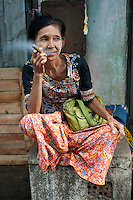 A woman in the Chinese market area of Yangon, Myanmar, relaxes with a cheroot, one of the country's main products.