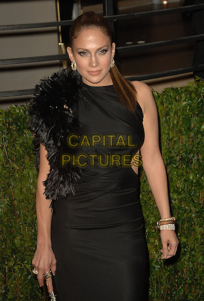 JENNIFER LOPEZ.The 2010 Vanity Fair Oscar Party held at The Sunset Tower Hotel in West Hollywood, California, USA..March 7th, 2010.oscars half length black dress silk satin cut out sides sleeveless feathers .CAP/RKE/DVS.©DVS/RockinExposures/Capital Pictures.