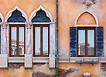 Yellow wall of antique Venetian building with old arched windows, rustic texture