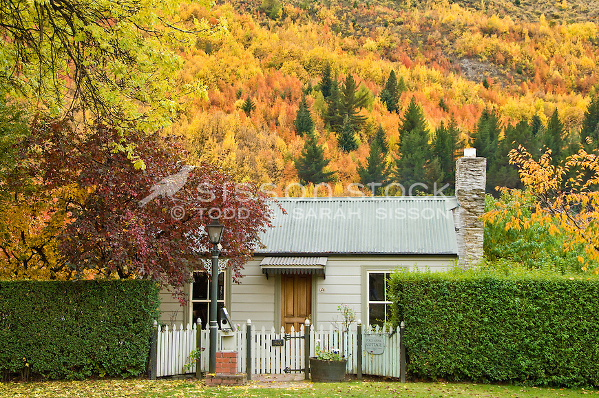 Autumn colours cover the hills behind an old cottage in historic Arrowtown, Central Otago, South Island