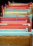 A group of brightly colored chairs leaning against a porch in an artistic manner. vertical composition
