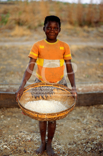 Mbati, Zambia. Girl with a basket of cassava flour.