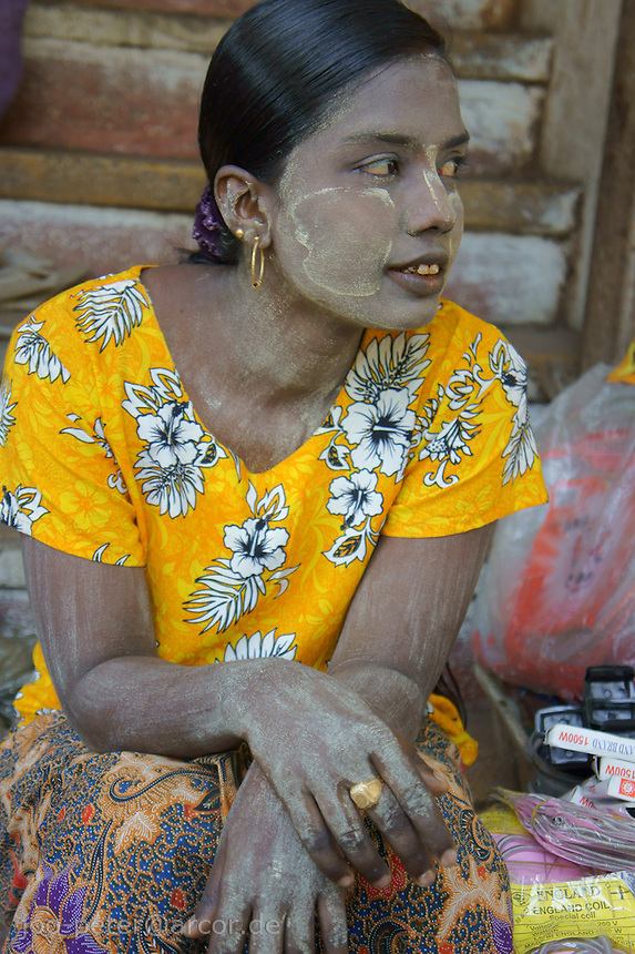woman with tanaka make-up, selling on the streets of Yangon, Myanmar, 2011