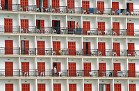 Spain. Mallorca in the Balearic islands. Colonia Sant Jordi. Early morning. tourists wake up in the hotel and open the red shutters to their balconies. © 1999 Didier Ruef