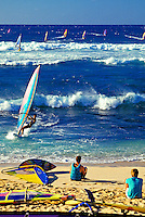 People on the beach watch the dozens of windsurfers cutting through the surf at world famous Hookipa each on Maui.