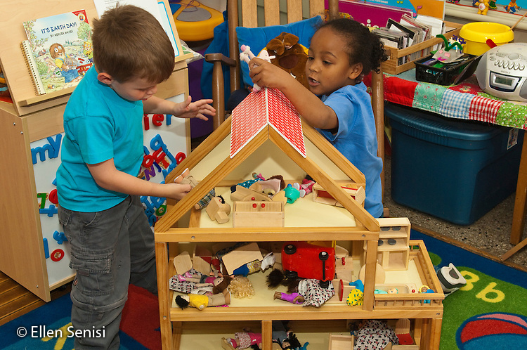 MR / Schenectady, New York. Fulton Early Childhood Education Center (urban public school early childhood education center). Pre-K classroom. Students (left: boy, 4, right: girl, 4, African-American Caucasian) playing with action figures from doll house at free playtime. ID: AI-gPd. MR: Dun6, Col12 ©Ellen B. Senisi