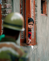 A girl looks sternly at police and military looking for stone throwers. Police clashed with stone throwing youth following the arrest of  separatist leader Yasin Malik. Srinagar, Kashmir, India. © Fredrik Naumann/Felix Features