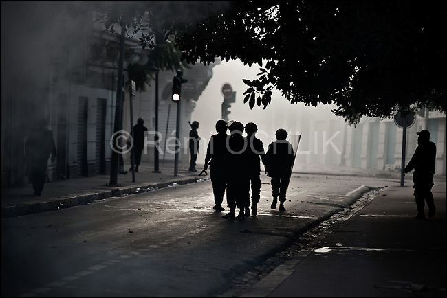 © Remi OCHLIK/IP3 - Tunis the 14 january 2011 - Tunisian anti riot policemen fire teargas against the demonstrators in a little street near Bourguiba avenue..Tunisia riots continued as President Zine El Abidine Ben Ali decided to dismiss his government following massive riots. The country's state news agency TAP says the president plans to call for new election in the next six months. Thousands of protestors took to the streets. The riots were sparked by high unemployment rates and a sagging economy as well as anger over government corruption. Tunisians enjoy little freedoms under President Zine El Abidine Ben Ali who has ruled a repressive regime for 23 years. Protestors ransacked buildings and threw rocks. Police used tear gas and gunshots to quell the crowd as protests got increasingly violent.