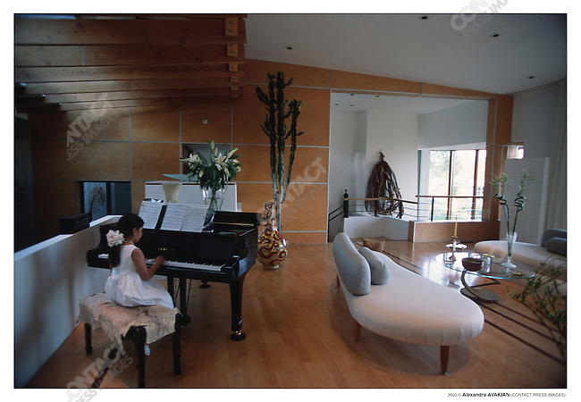 Girl of Iranian ancestry plays piano at family-home; Los Angeles, California, April 2002.