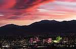 An amazing sierra wave cloud sunset lights up the sky over the casino strip in downtown Reno, Nevada with Mt. Rose and the sierra in the background.