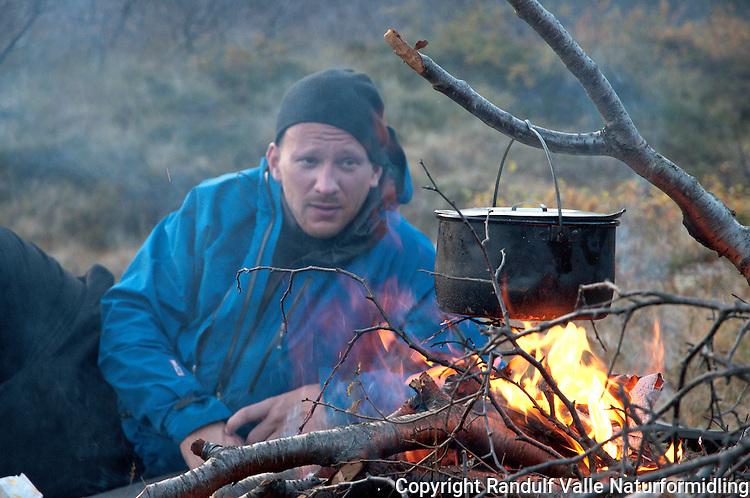 Mann slapper av foran bålet. ---- Man relaxing in front of camp fire.