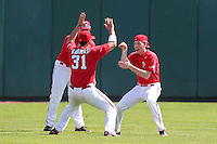 Stephen Rivera #22 (hidden/back), Paul Karmas #31 and Eddie Medina #12 of the St. John's Red Storm play their version of rock, paper, scissors, before a game in the Big East-Big Ten Challenge vs. the Michigan Wolverines at Al Lang Field in St. Petersburg, Florida;  February 19, 2011.  St. John's defeated Michigan 13-6.  Photo By Mike Janes/Four Seam Images