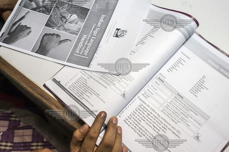 A student reads course books while attending classes at the Noida Deaf Society.