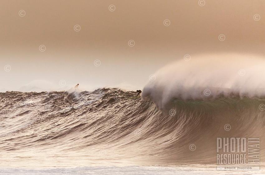 A surfer drops into a huge wave as a jet skier goes over the shoulder, Waimea Bay, O'ahu.